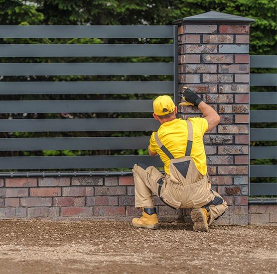Zdjęcie pracownika montującego ogrodzenie